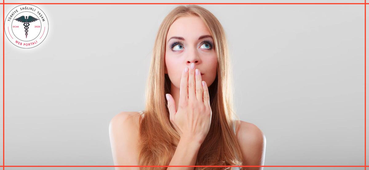 ağzı kokan kadın, kadının ağzı kokuyor, ellleriyle ağzını kapatan kadın, şaşırmış kadın, yukarı bakan kadın,